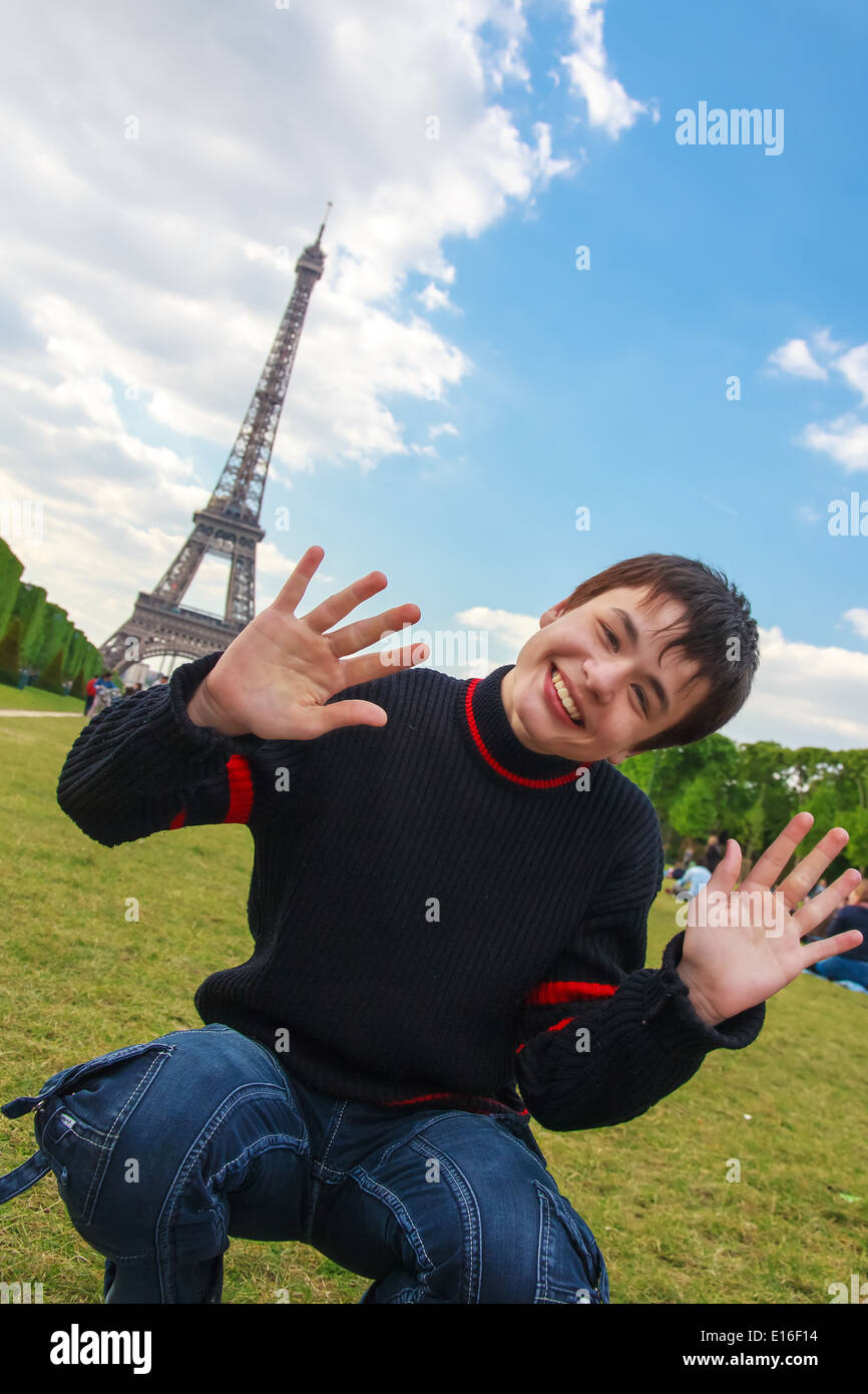 Teenager laughing, playing and fooling around on the Champ de Mars in front of the Eiffel Tower (La Tour Eiffel) in Paris - Stock Image