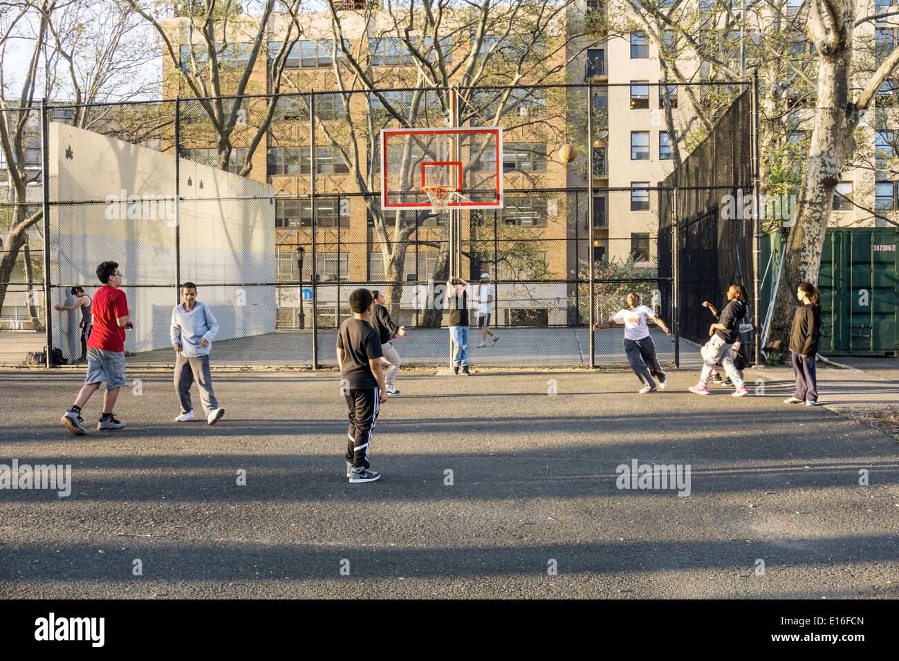 teen black girl aims for the basket in a good natured unisex street basketball game in DeWitt Clinton park Hells Kitchen - Stock Image