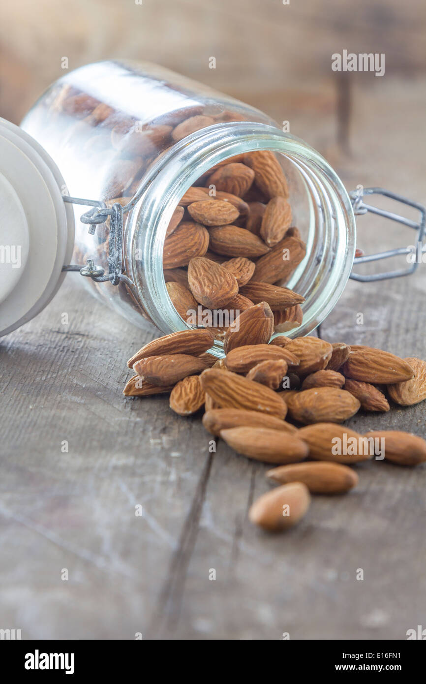 almonds in a jar on a wooden table - Stock Image
