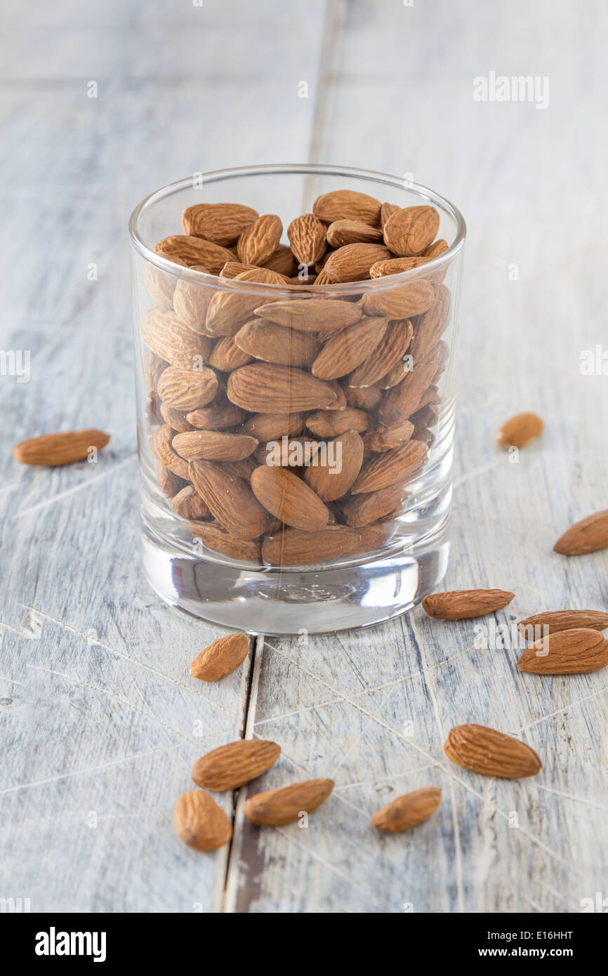 almonds in a glass on a wooden table - Stock Image