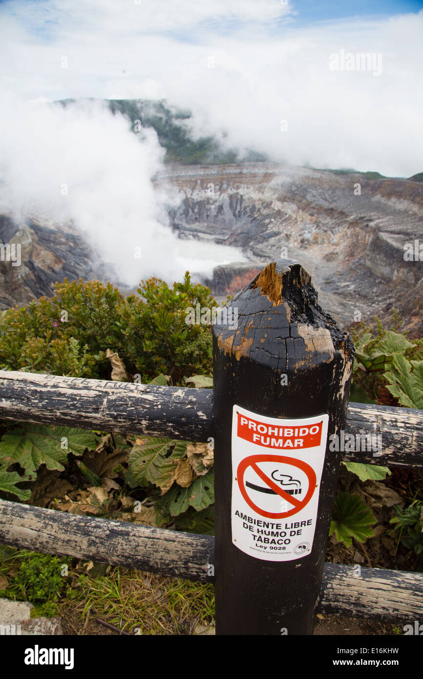 Ironic Smoking Prohibited sign next to the smoking volcanic vent of Poas volcano in central Costa Rica - Stock Image