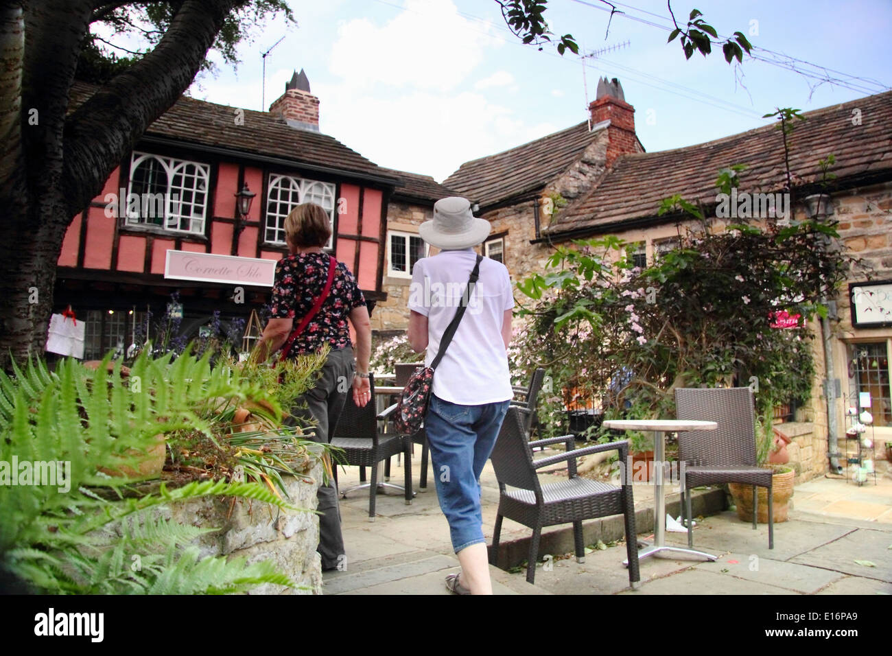 Tourists peruse the shops in King's Court, Bakewell, Peak District, Derbyshire, England, UK - summer - Stock Image