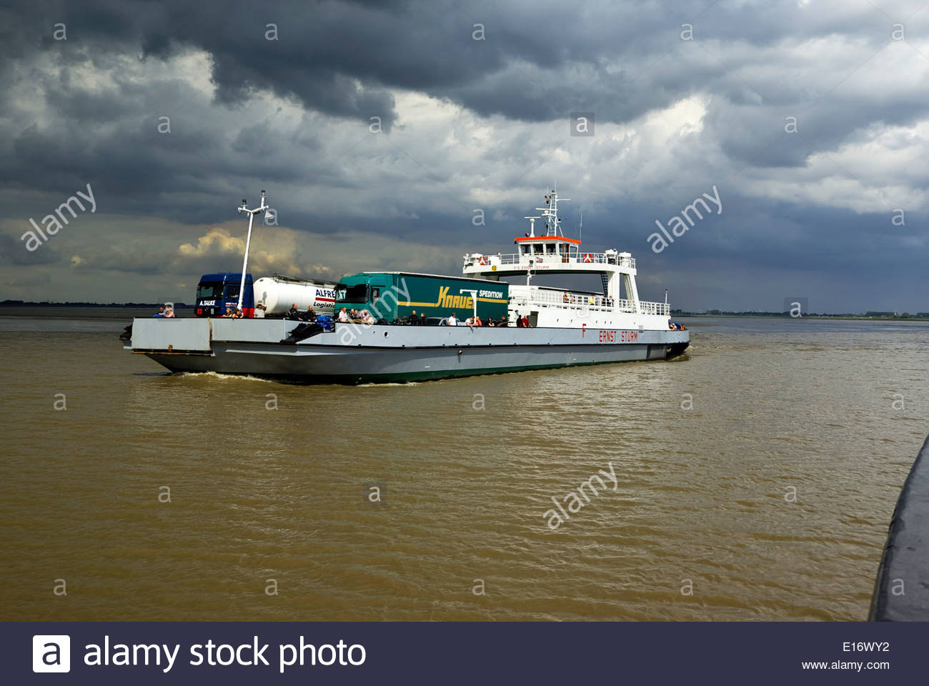 The ferry Ernst Sturm crosses the Elbe River north of Hamburg, from Wischhafen to Glückstadt, carrying vehicles and passengers. - Stock Image