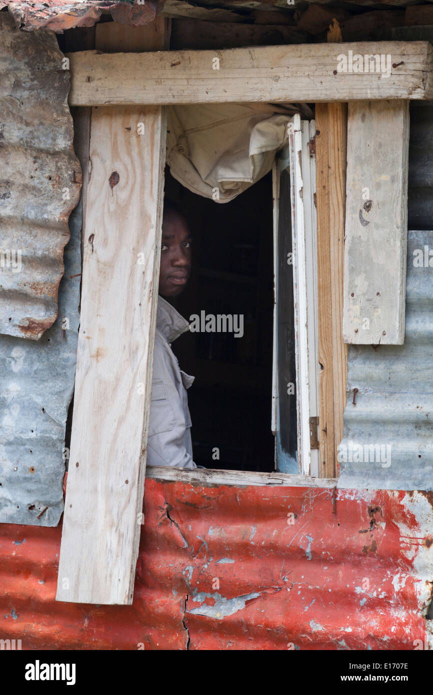 Boy looking out of a window in Imizamo Yethu Township (Mandela Park), Cape Town, South Africa Stock Photo