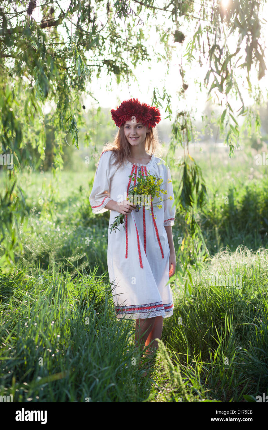 Young woman posing in traditional ukrainian costume outdoors - Stock Image