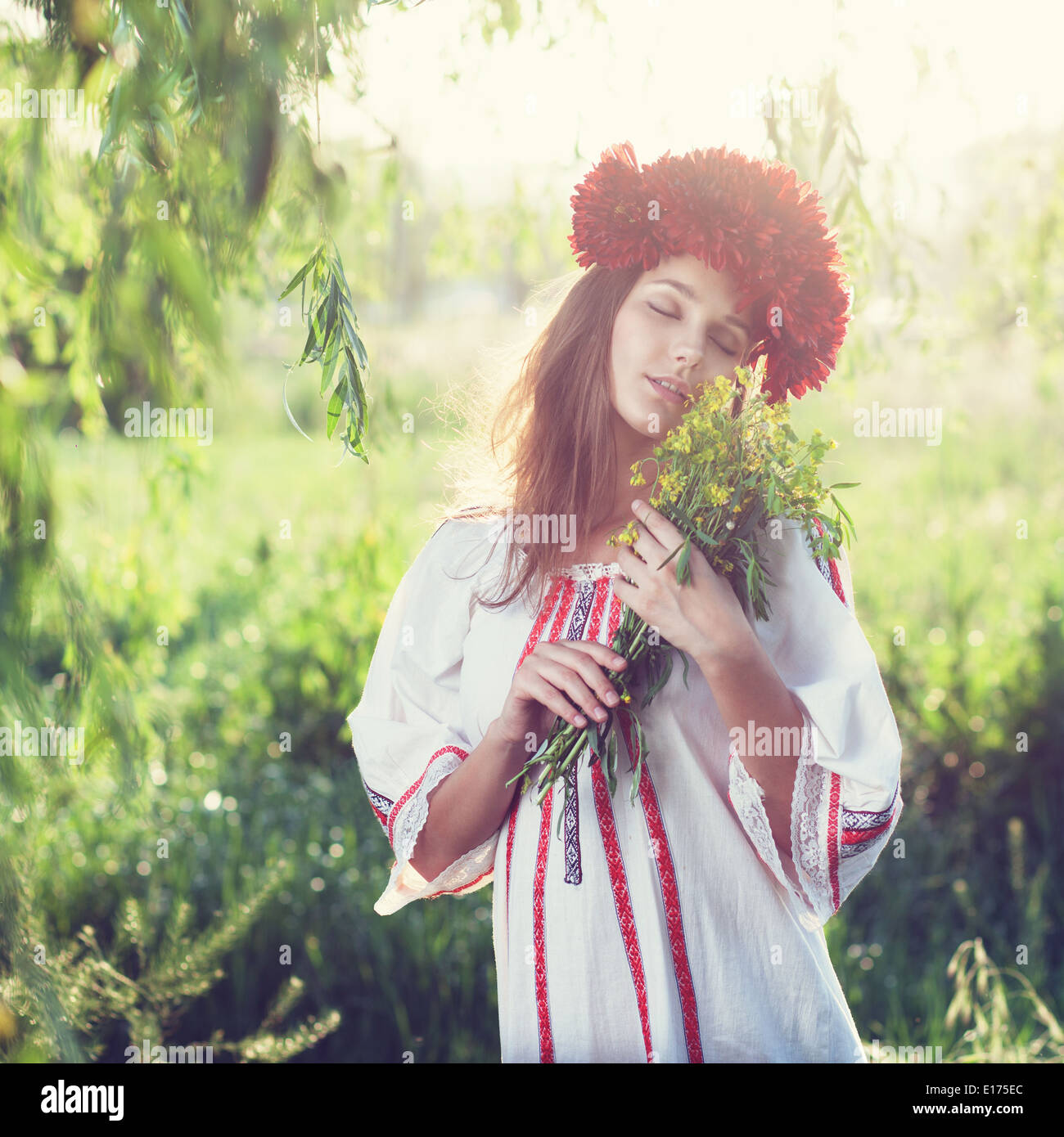 Emotional portrait of ukranian woman with bouquet of flowers - Stock Image