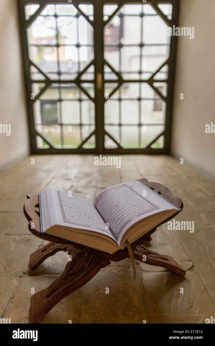 Quran on lectern faldstool in front of old window in mosque - Stock Image
