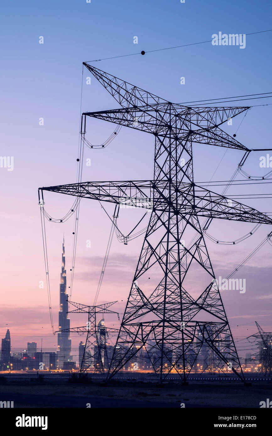 Electricity transmission lines and pylons and skyline at dusk in Dubai United Arab Emirates - Stock Image