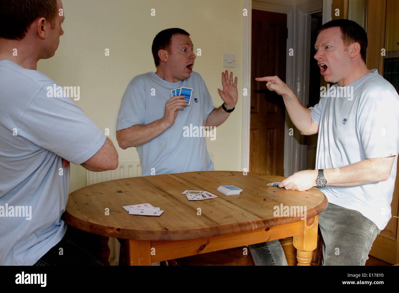 A funny card cheating scene featuring the same person three times - Stock Image