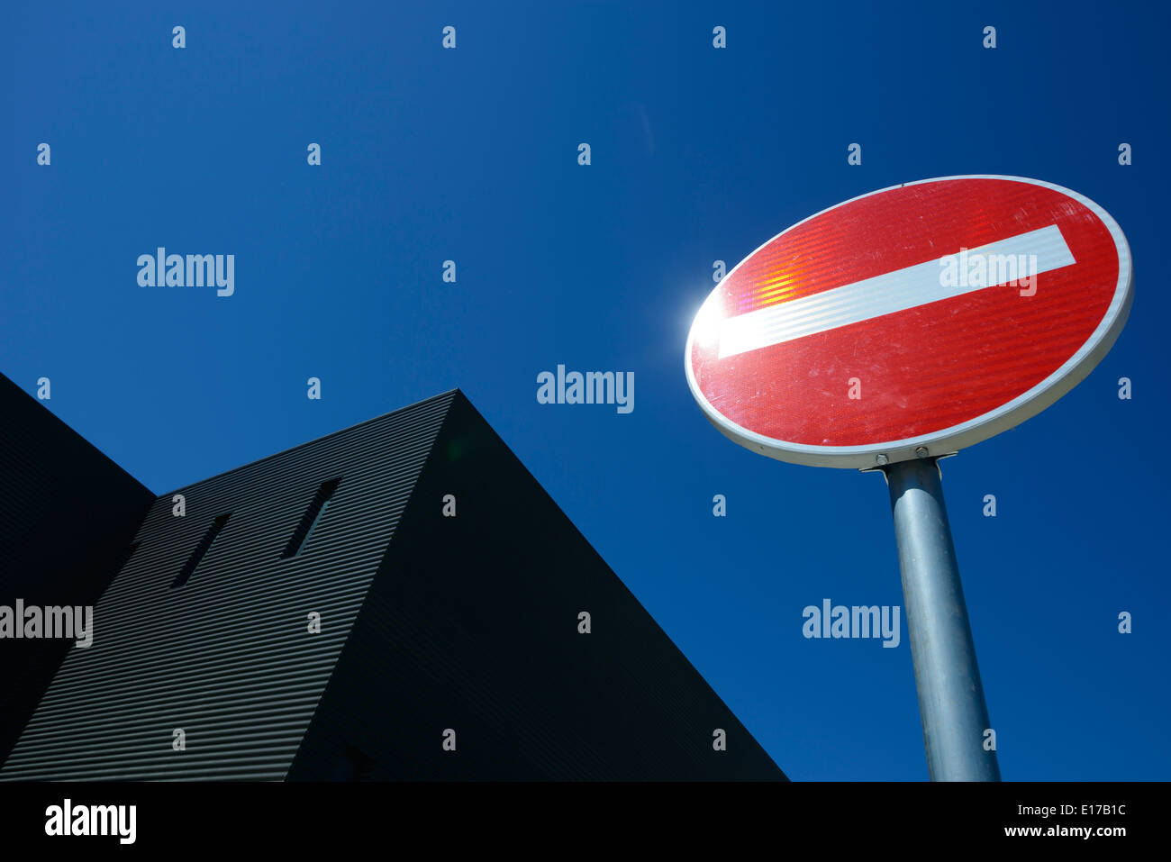 No entry road sign against a clear blue sky - Stock Image