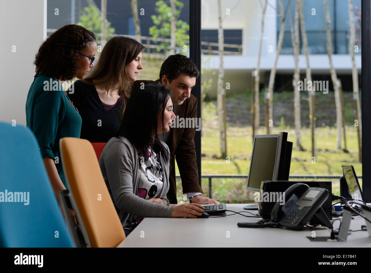 Office workers discussing a project while looking at a computer screen - Stock Image
