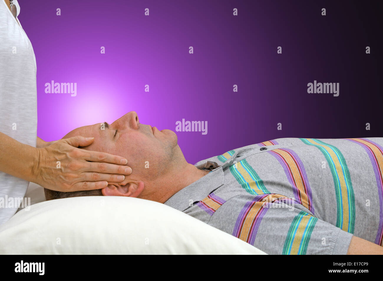Female healer channeling healing energy to male client on a purple background - Stock Image
