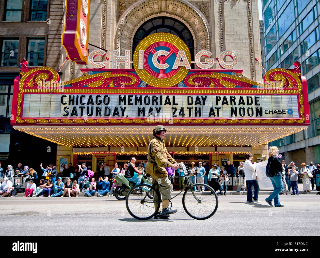 A veteran in WWII uniform rides a bicycle past the Chicago Theatre during a Memorial Day Parade down State Street  May 24, 2014 in Chicago, Illinois. - Stock Image