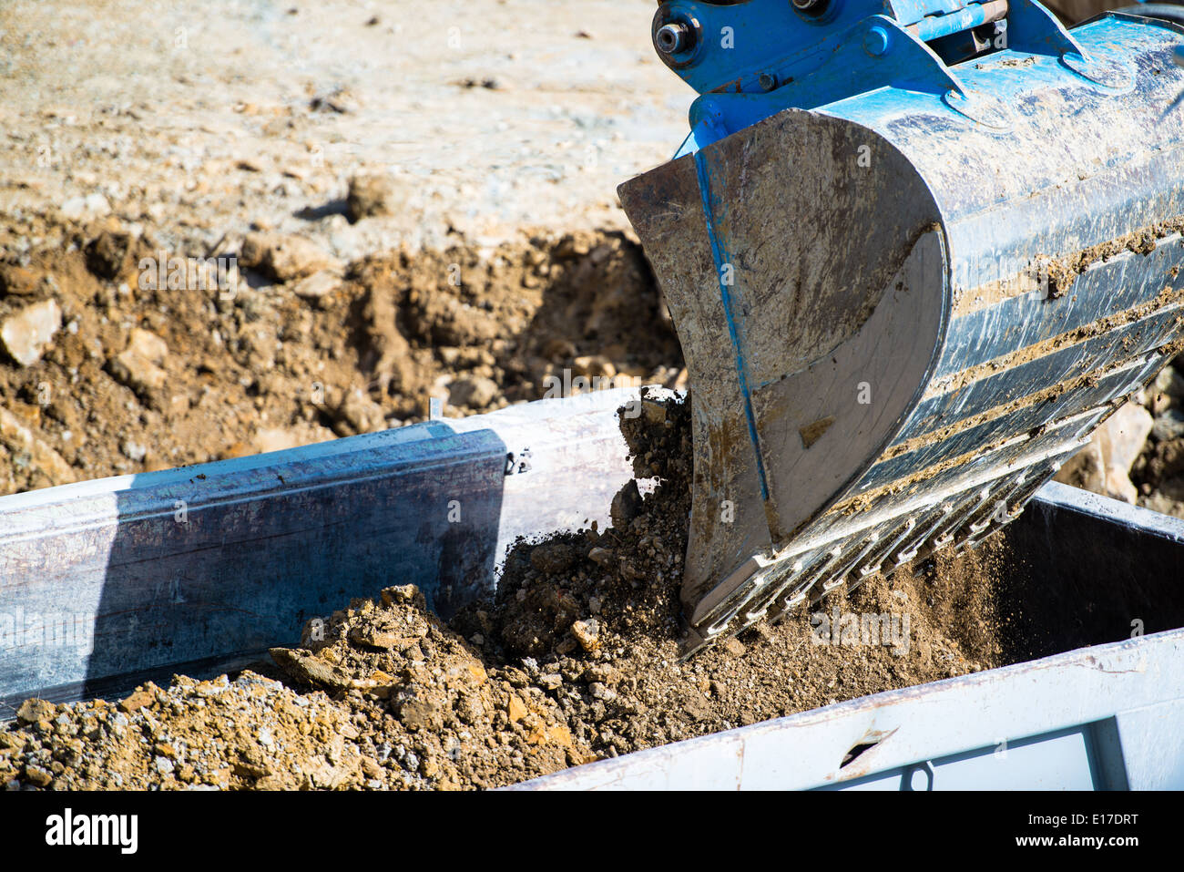 Closeup of dump truck being filled by excavator - Stock Image