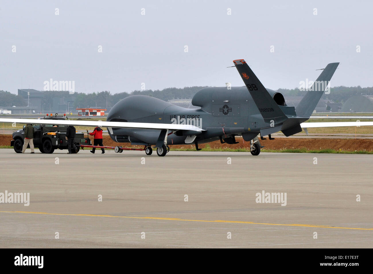 A US Air Force RQ-4 Global Hawk unmanned aerial drone is towed after landing for the first time on Japanese territory at Misawa Air Base May 24, 2014 in Aomori Prefecture, Honshu, Japan. - Stock Image