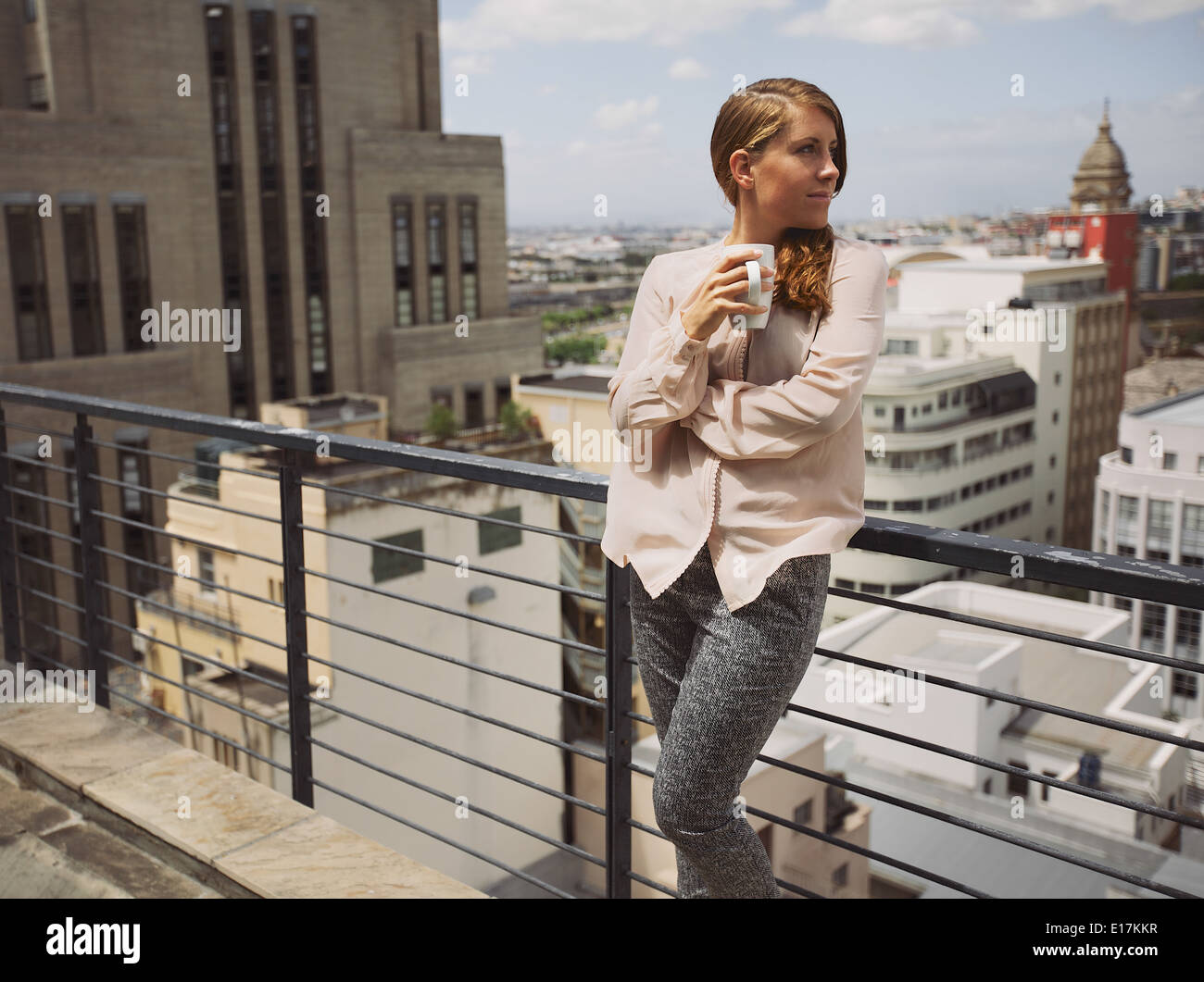 Beautiful young lady standing by a railing on terrace holding a cup of coffee looking away. Caucasian female drinking Stock Photo