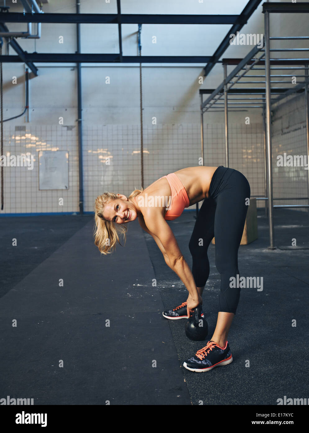 Female fitness model exercising with kettle bell at gym. Happy young caucasian woman doing crossfit workout. - Stock Image