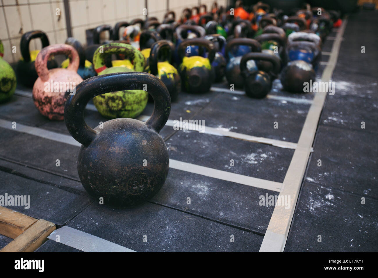 Different sizes of kettlebells weights lying on gym floor. Equipment commonly used for crossfit training at fitness club - Stock Image