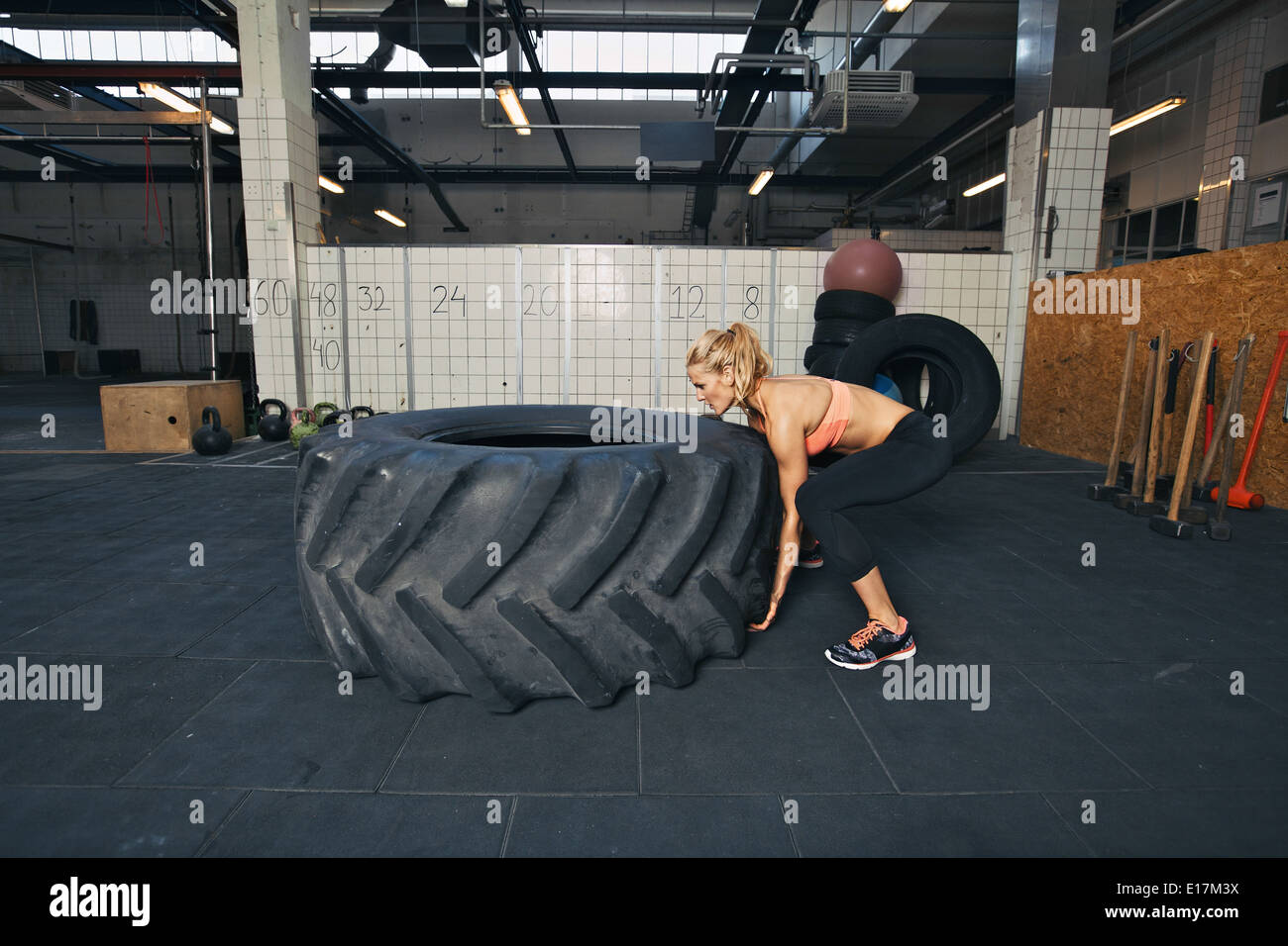Tough female athlete flipping a huge tire. Young woman doing crossfit exercise at gym. - Stock Image
