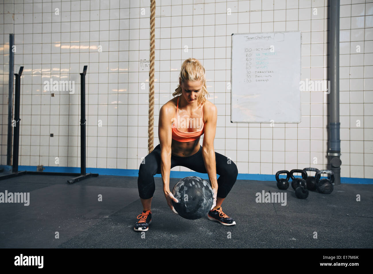 Fit and strong female athlete working out with a medicine ball to get better core strength and stability. Woman doing exercise. - Stock Image