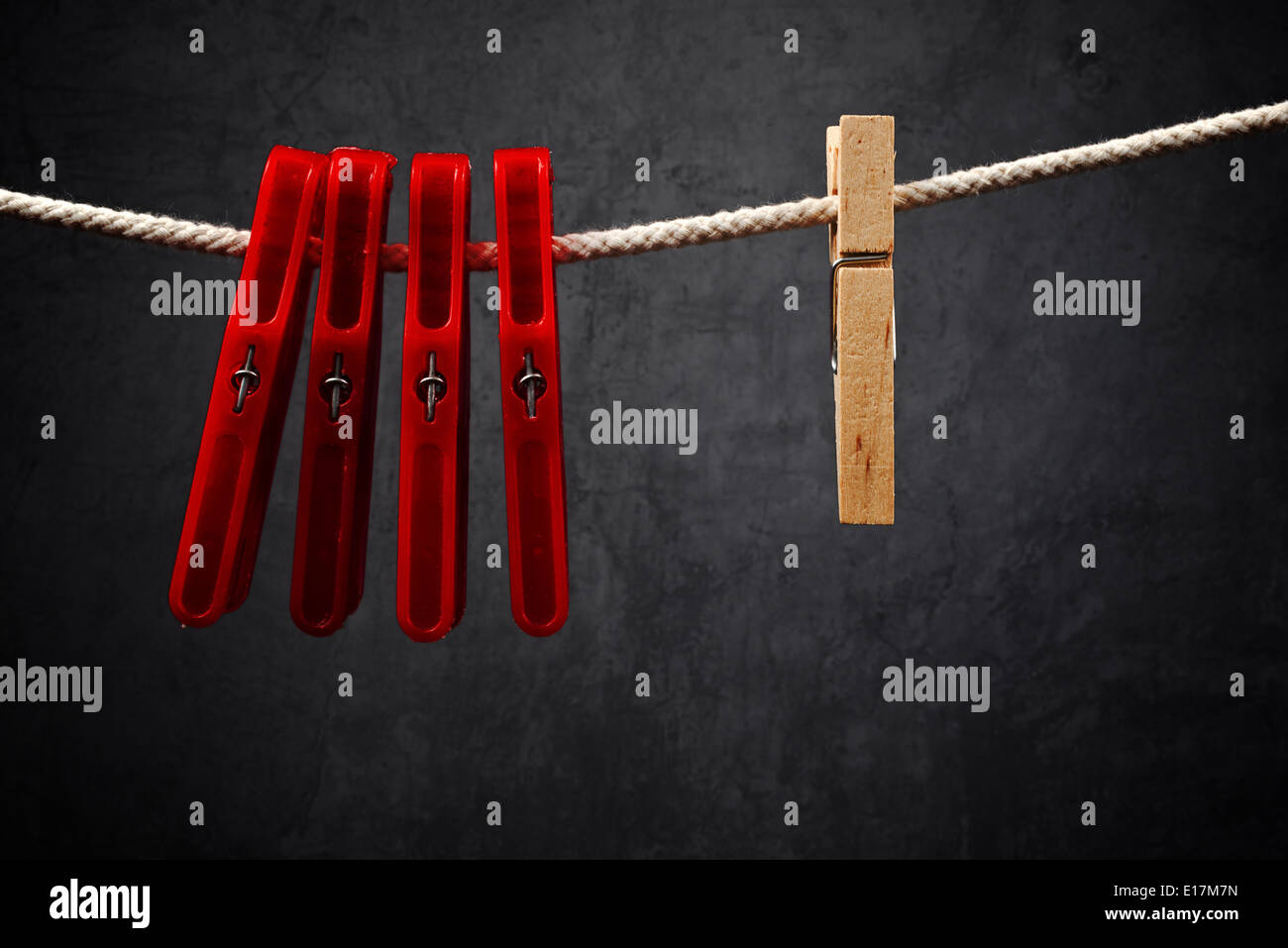 Clothes pins on the rope. Wooden one is Standing out from the crowd. - Stock Image