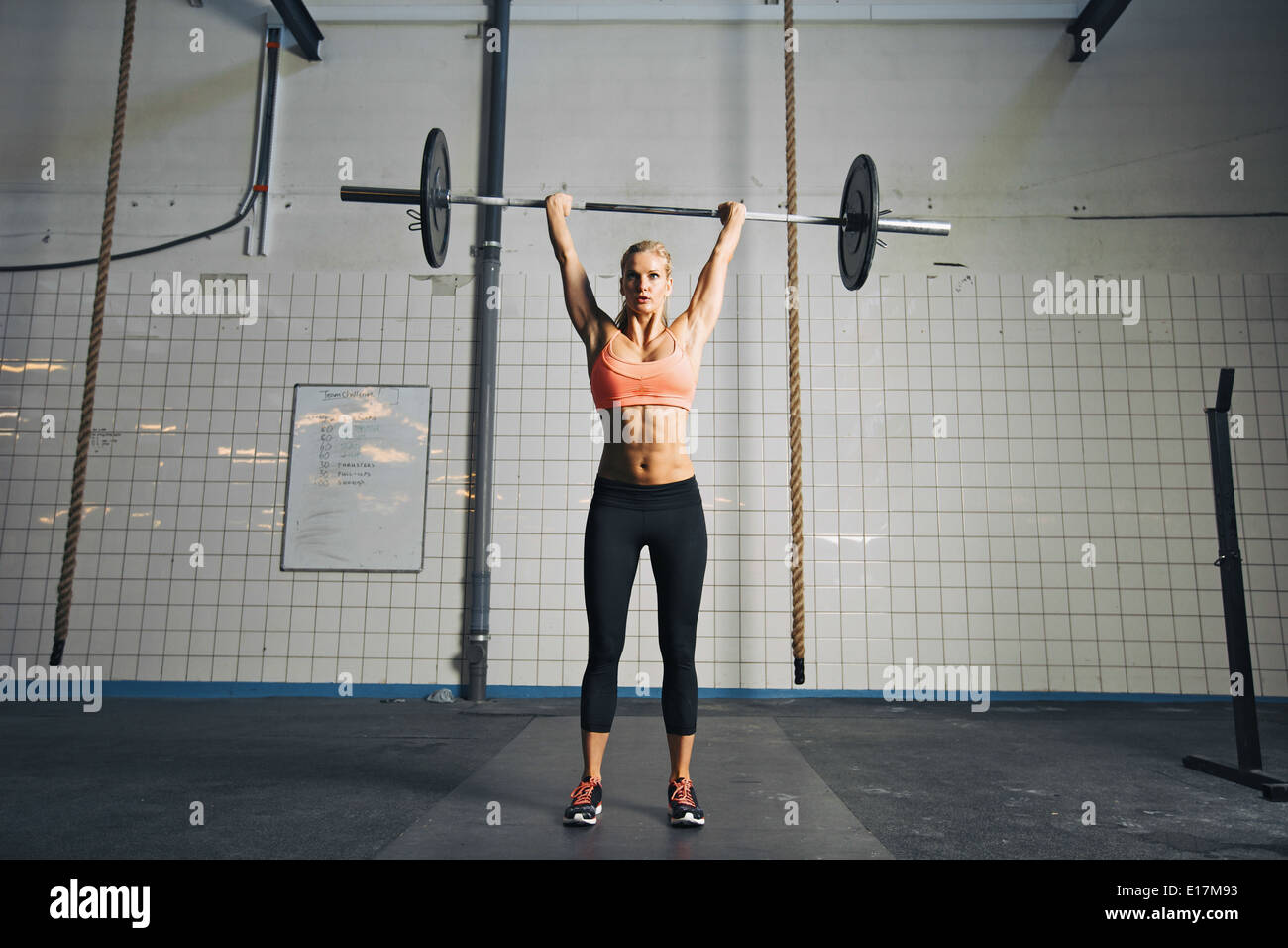 Full length image of strong young woman with barbell and weight plates overhead doing crossfit exercise. Fit female athlete. - Stock Image