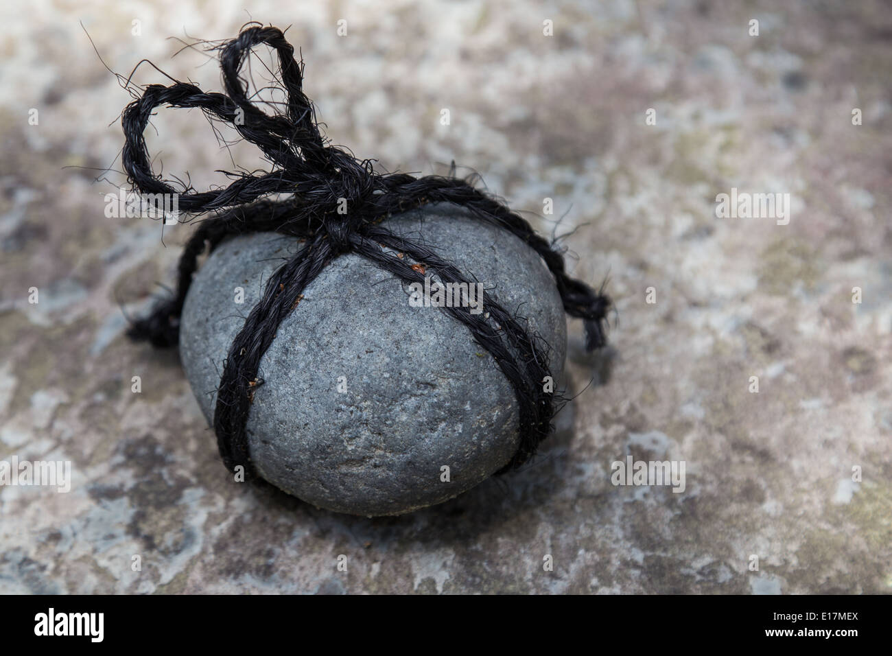 Tome Ishi is a stone is wrapped in rope and placed in a path or in front of a gate. It means 'do not enter'. - Stock Image