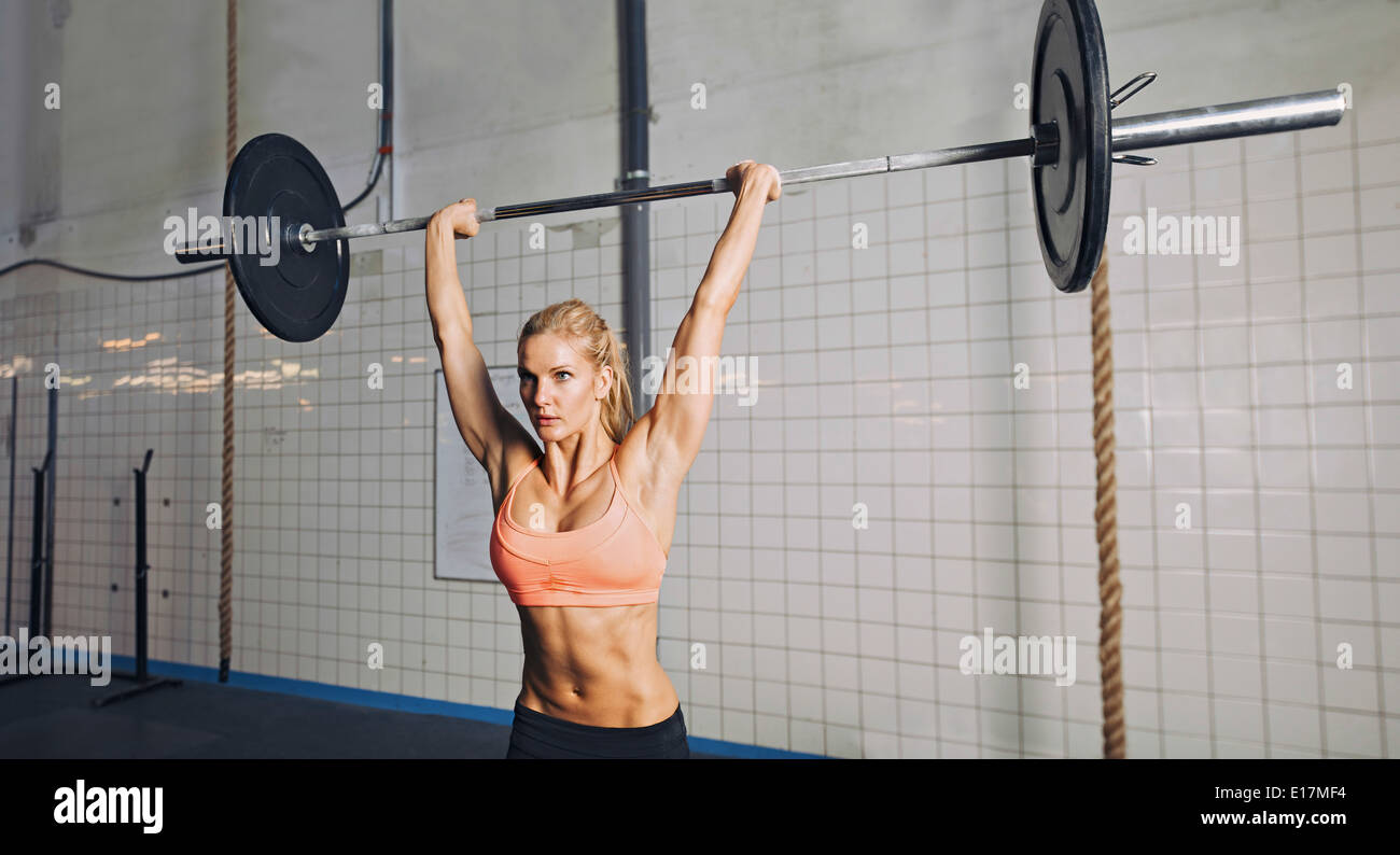 Muscular young woman doing weightlifting at crossfit gym. Fit female model lifting heavy weights at gym. - Stock Image