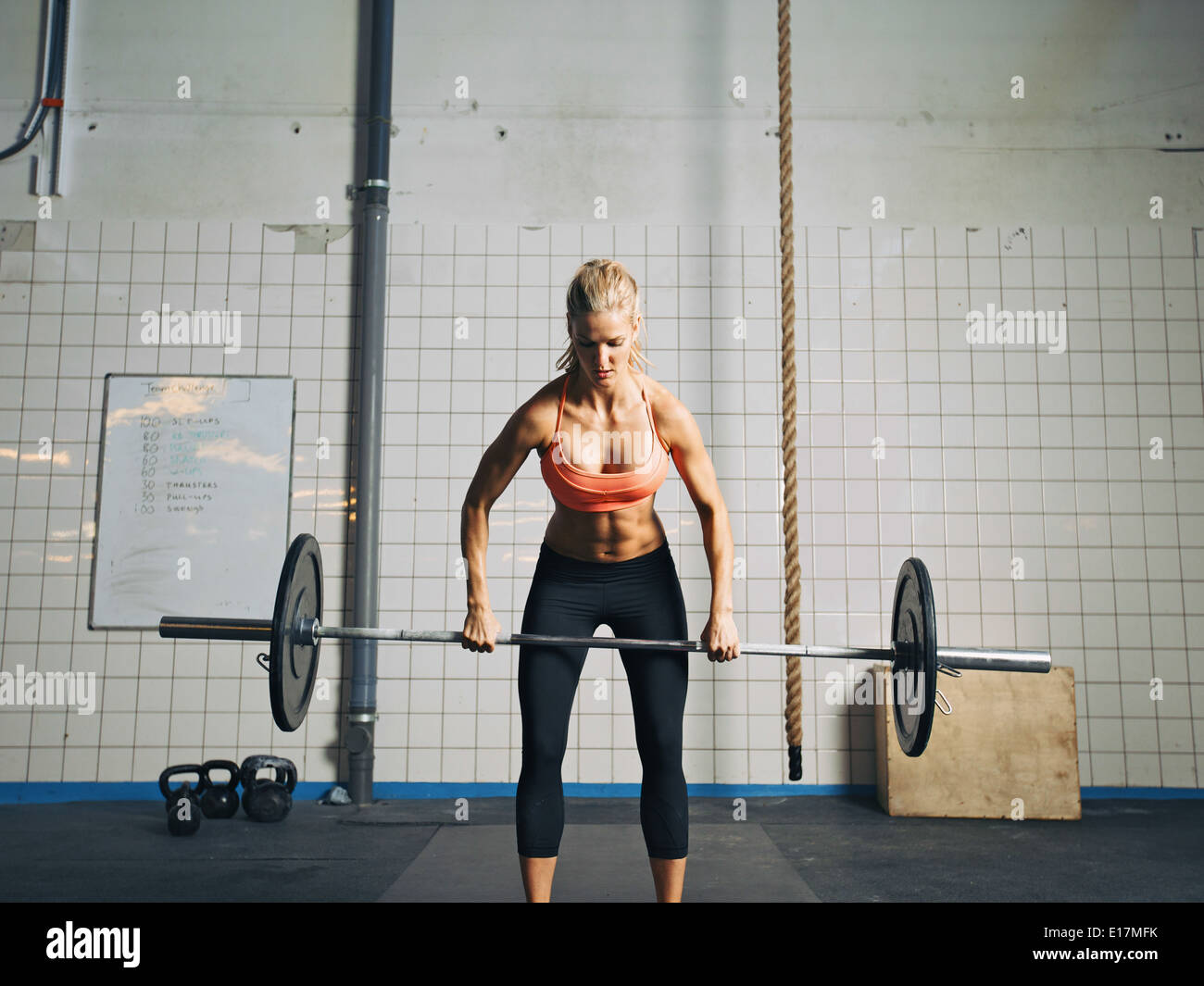 Fit and attractive caucasian female holding a barbell in her hands. Crossfit woman lifting heavy weights in gym. - Stock Image