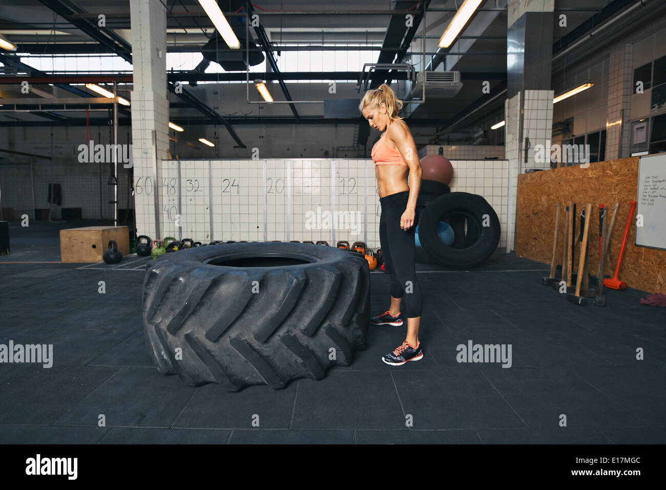 Strong young woman athlete standing and looking at huge tire at gym. Fit female athlete performing tire flipping exercise. - Stock Image