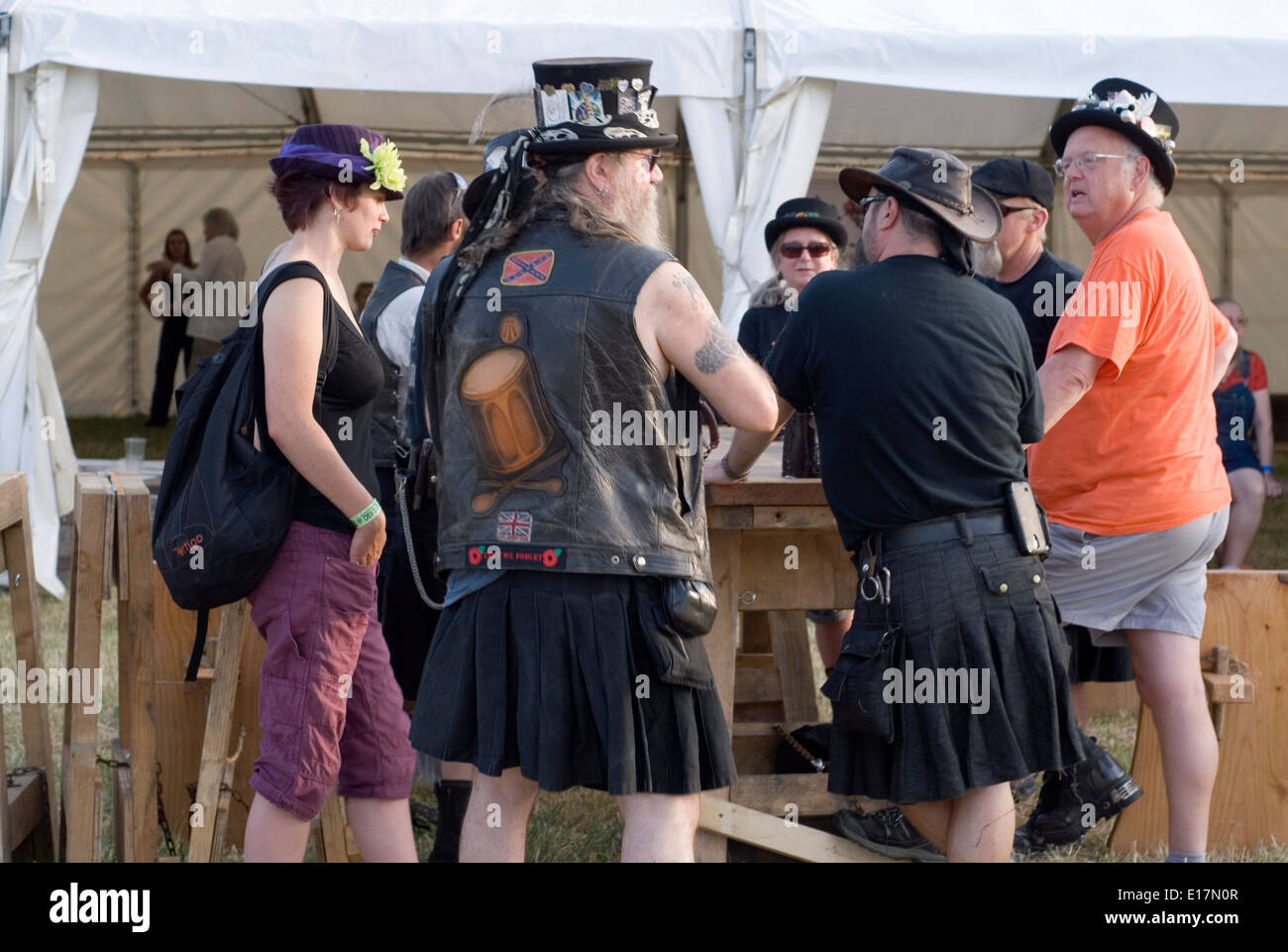 Tewkesbury Medieval Festival, July 2013: revelers at the beer tent in strange costume of leather, kilts and top hats - Stock Image