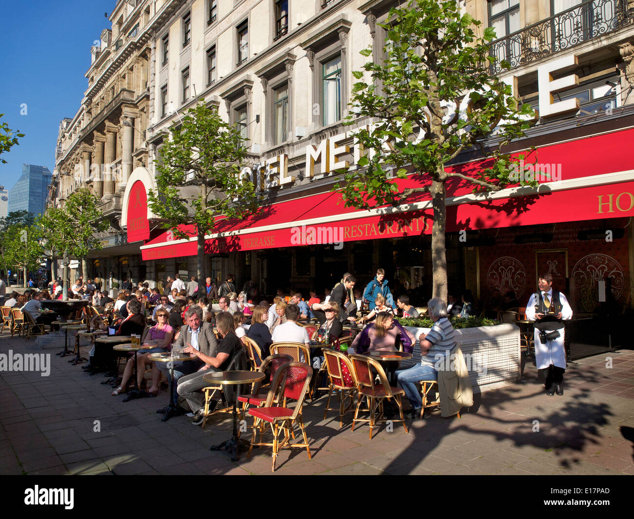 People enjoying the afternoon sun in front of the famous Hotel Metropole in Brussels, Belgium - Stock Image