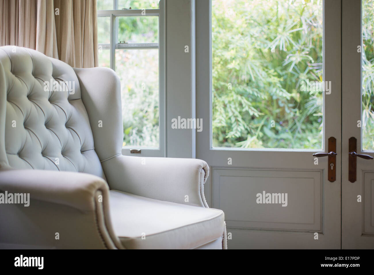 Tufted wingback chair near window - Stock Image