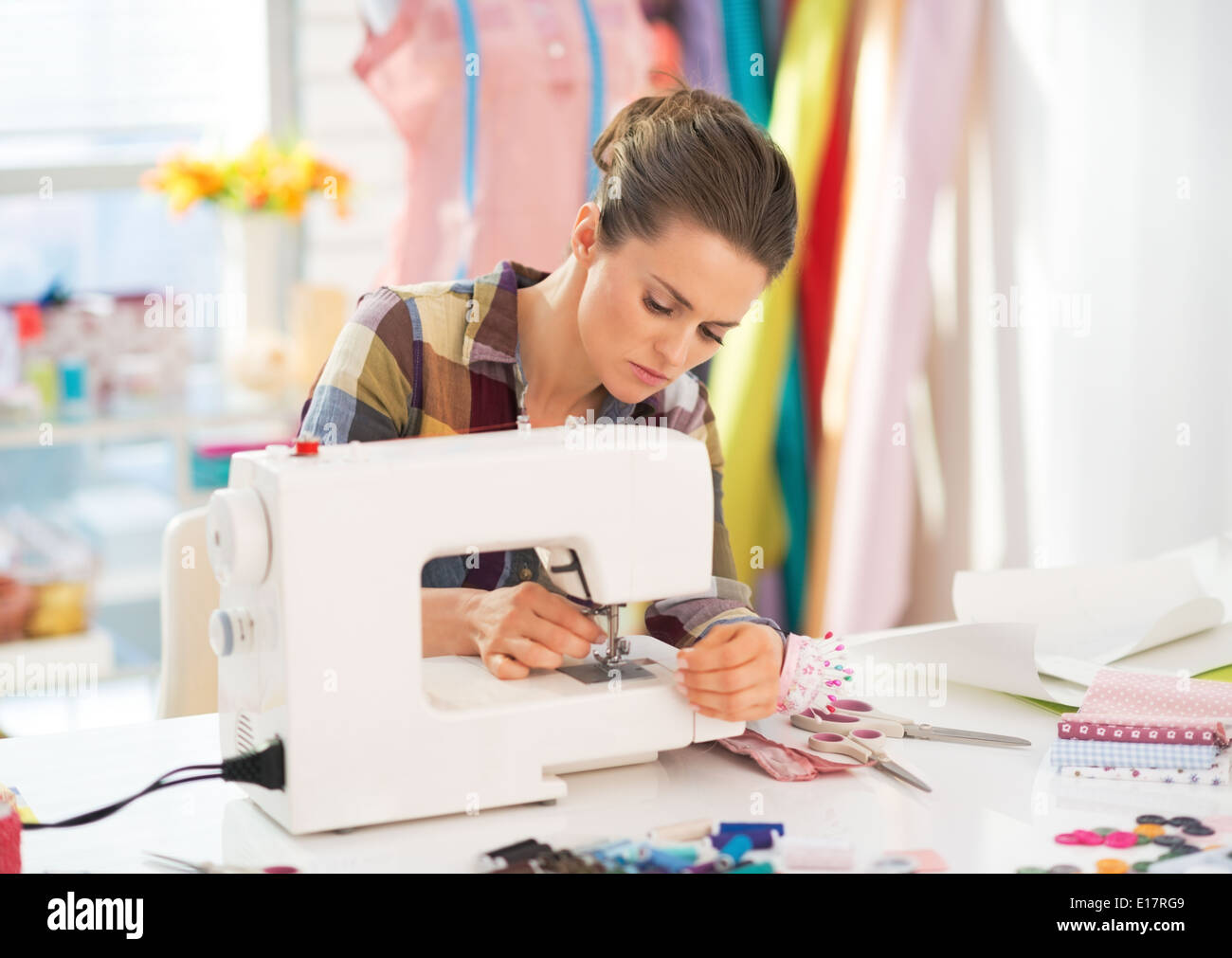 Seamstress working with sewing machine - Stock Image