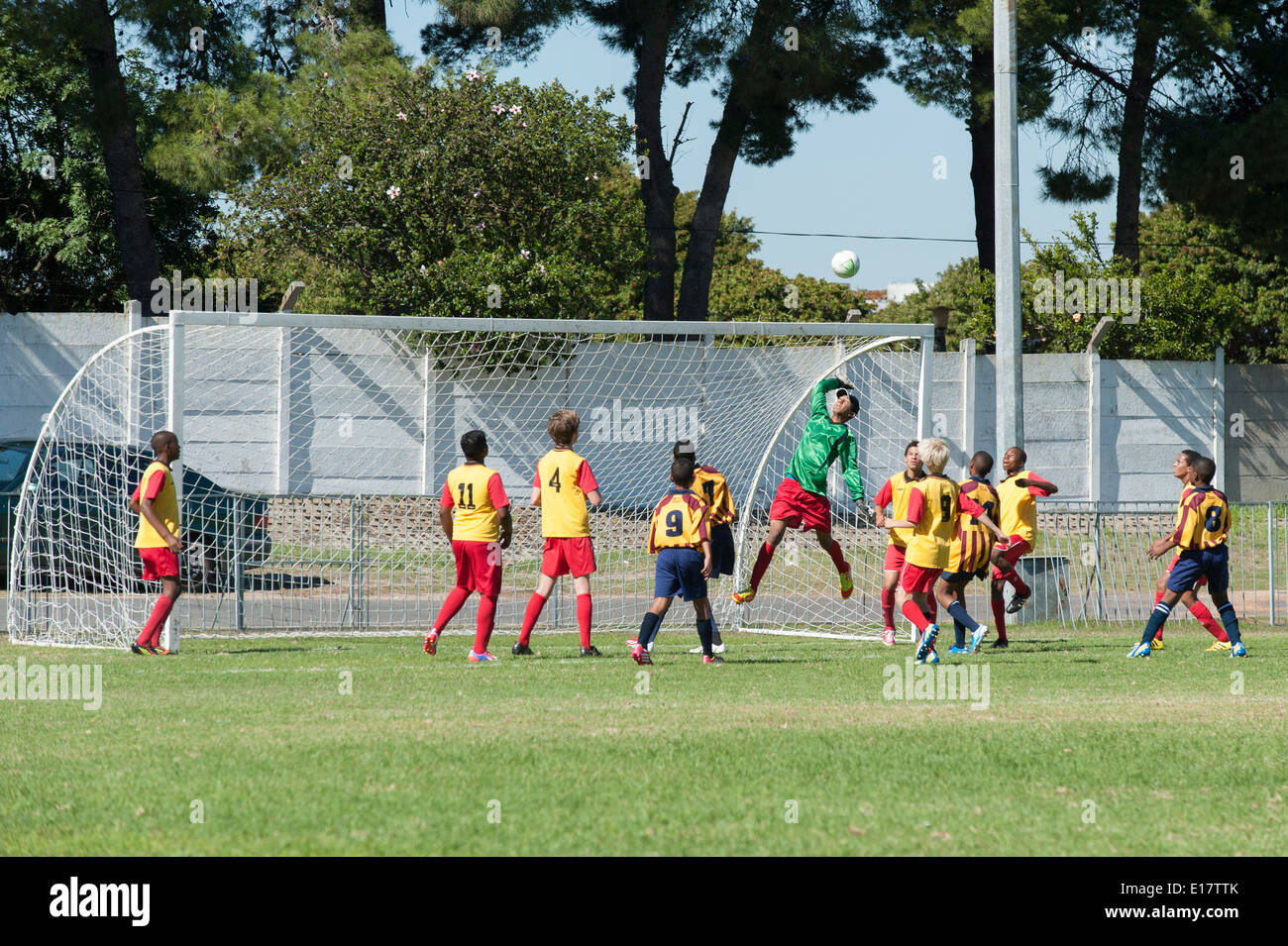 Goalkeeper jumping in the air other football players watching the ball, Cape Town, South Africa - Stock Image