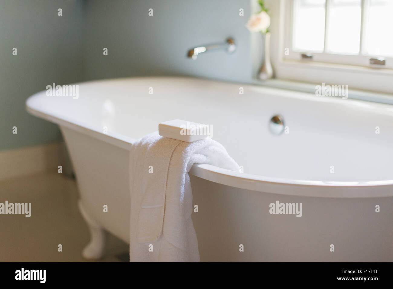 Bar soap and towel on ledge of claw foot tub - Stock Image
