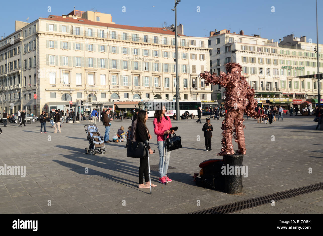 Tourists Watching Living Sculpture Performing or Street Theater on the Quay or Quai des Belges Marseille or Marseilles France - Stock Image