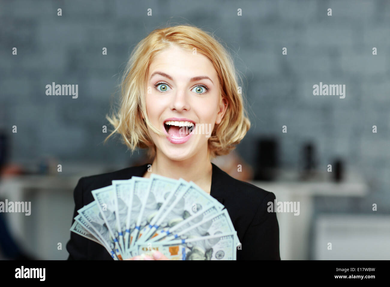 Young businesswoman holding money with delight - Stock Image