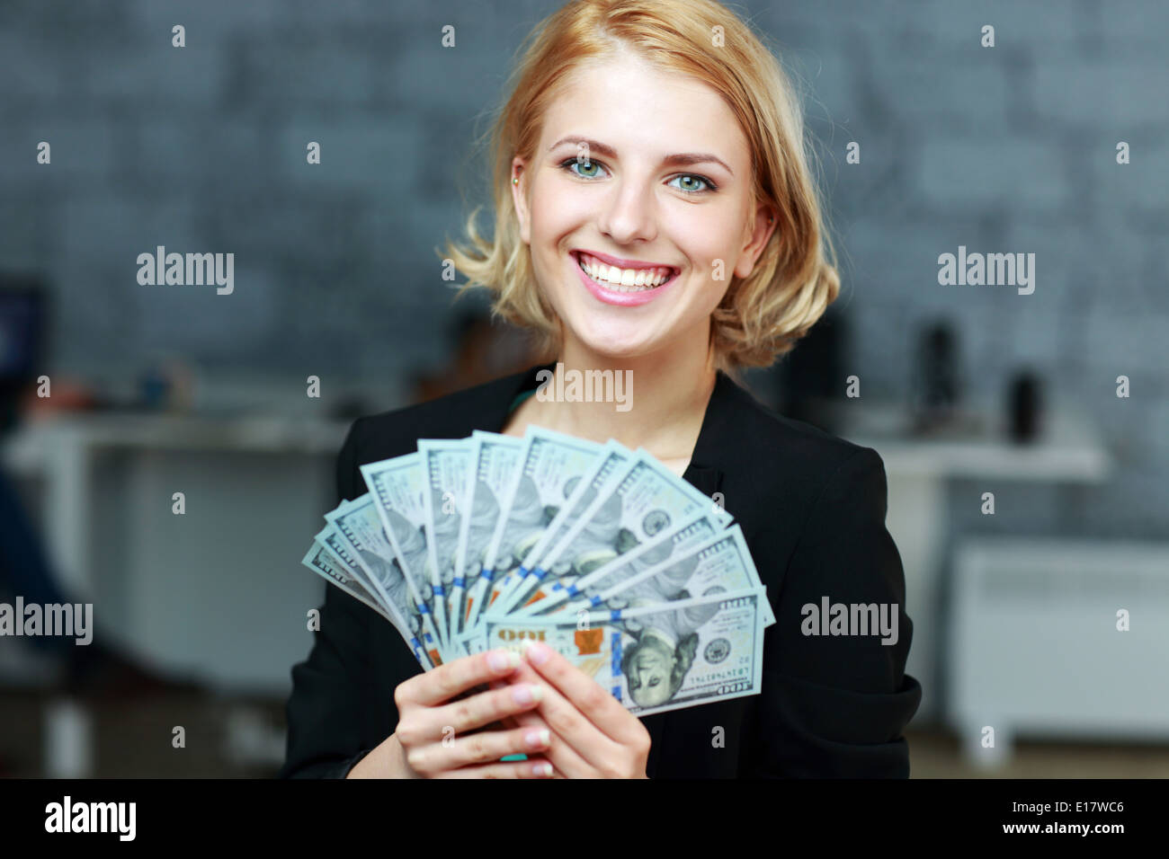 Happy smiling businesswoman holding bills of dollars in office - Stock Image