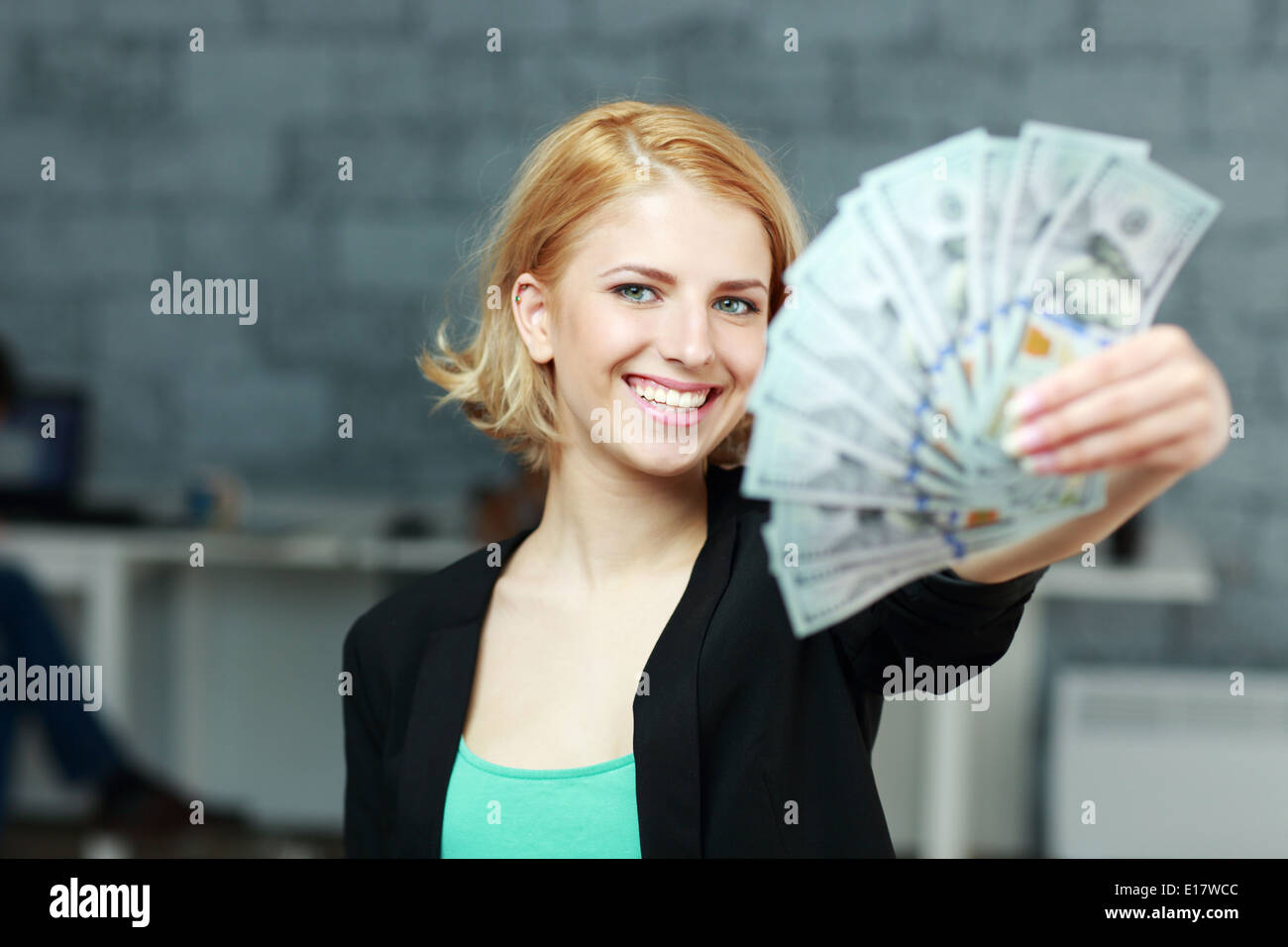 Young happy businesswoman holding bills of dollars in office - Stock Image