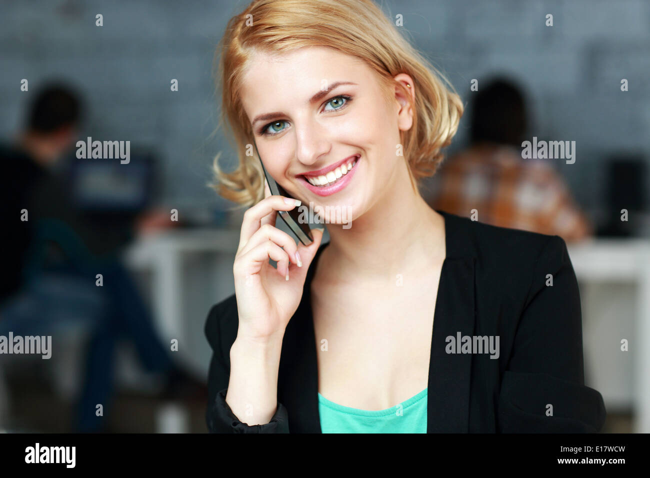 Happy businesswoman talking on the phone in office - Stock Image
