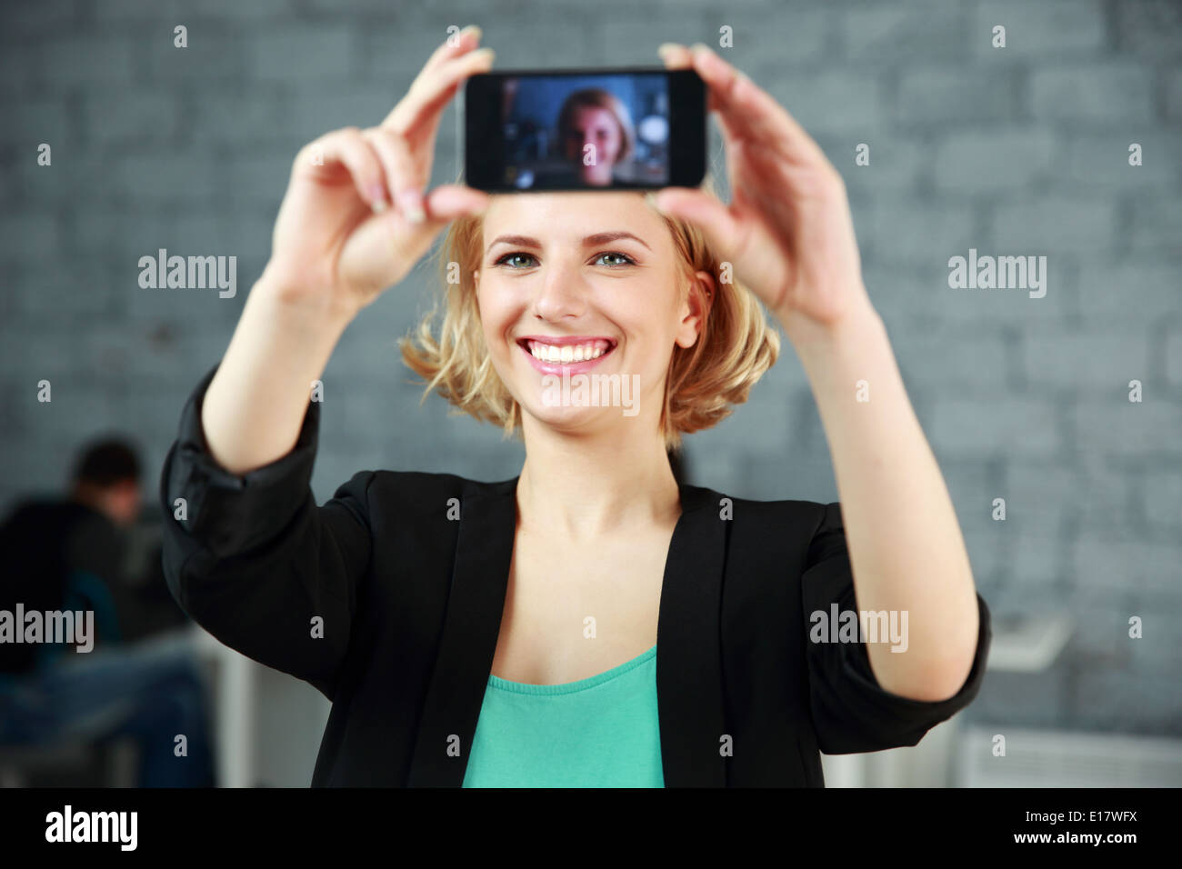 Young happy woman making a self photo by her smartphone in office - Stock Image
