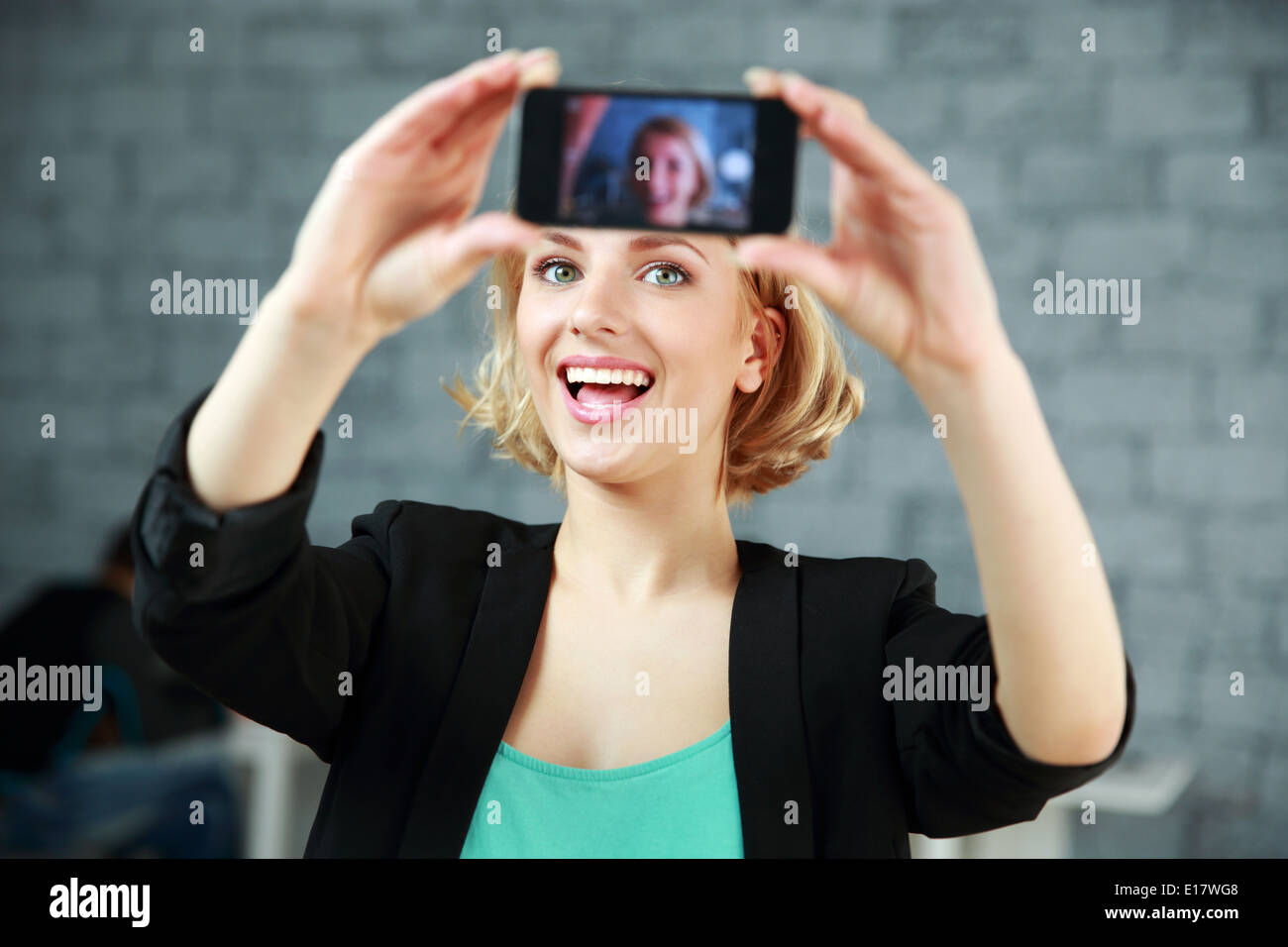 Young laughing woman making a self photo by her smartphone in office - Stock Image