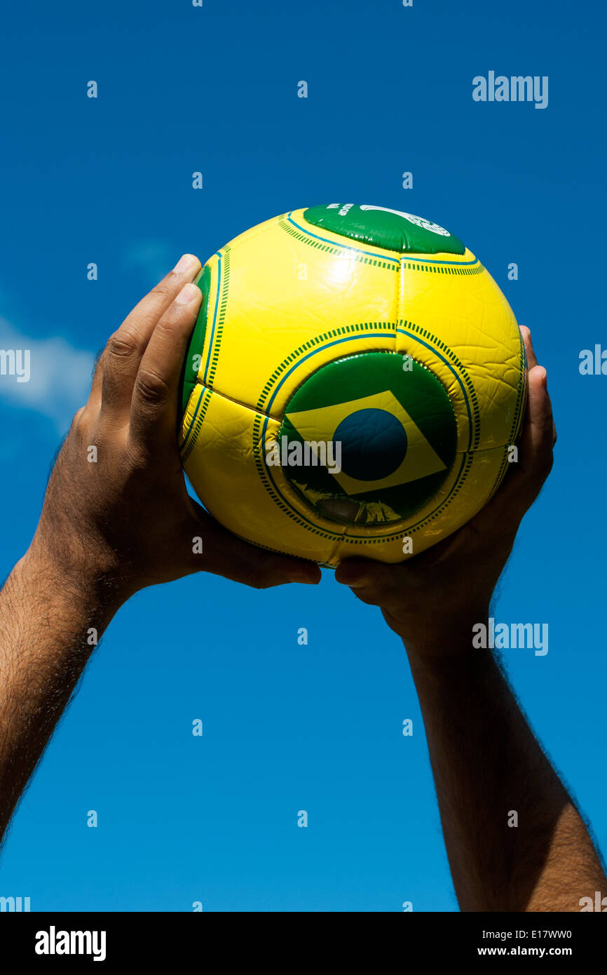 Man throwing Brazilian football for World Cup 2014 - Stock Image