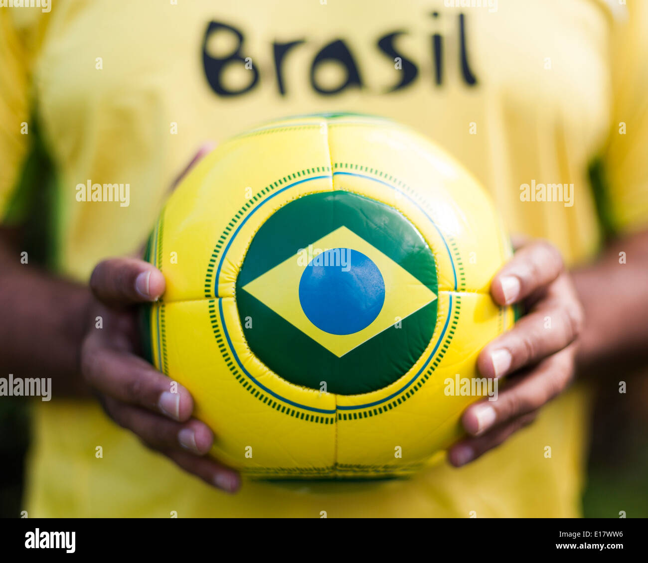 Man holding football with Brazilian flag for Brazil World Cup 2014. Stock Photo