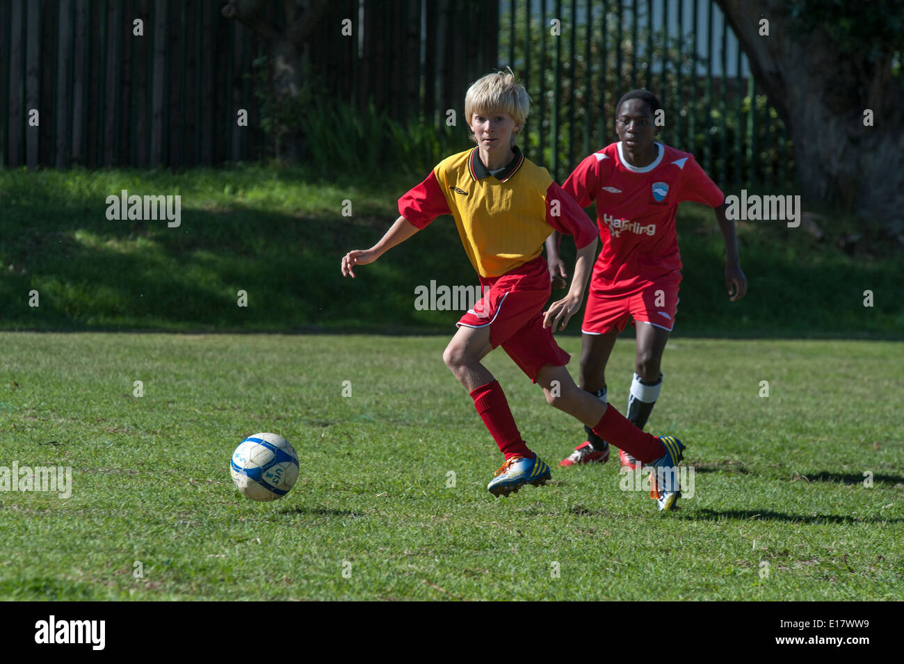 Junior football players running with the ball, Cape Town, South Africa - Stock Image