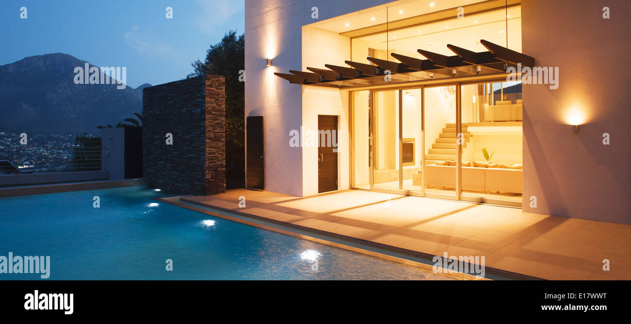 Illuminated modern house overlooking swimming pool - Stock Image