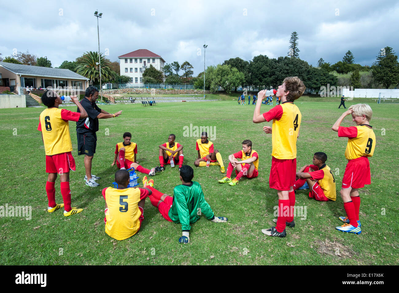 Coach instructing junior football team during the break, Cape Town, South Africa - Stock Image