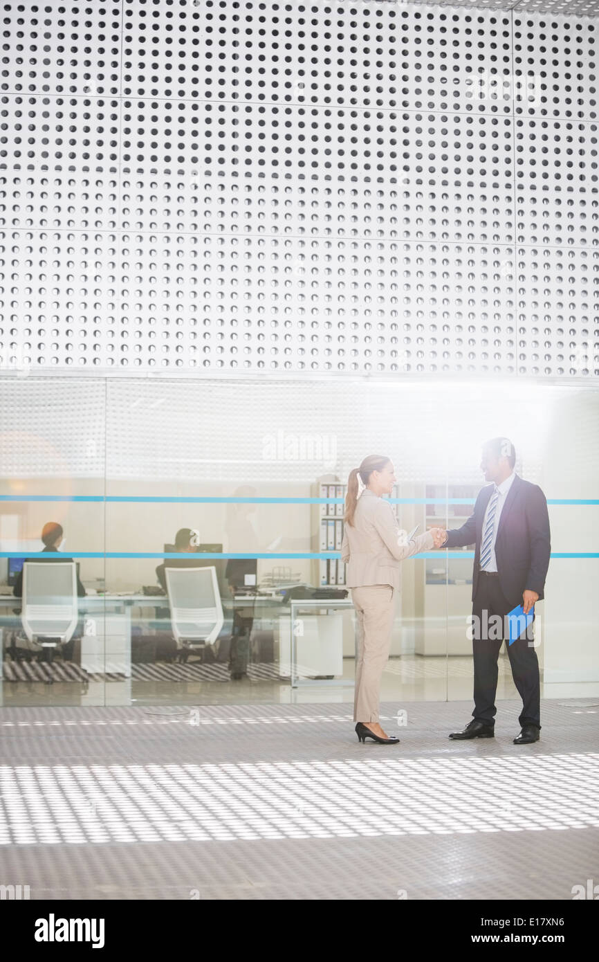 Businessman and businesswoman handshaking outside office - Stock Image