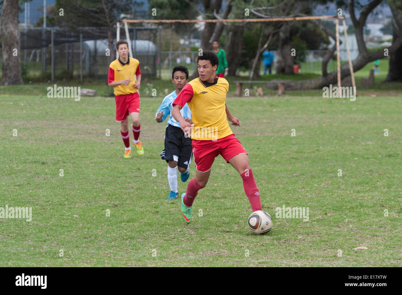 Junior football player running with the ball, looking where to pass, Cape Town, South Africa - Stock Image